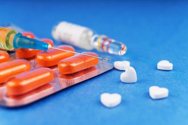 Tabuletas em uma bolha, em uma seringa com a preparação médica datilografada, em uma ampola com uma preparação farmacêutica e em  imagem de stock