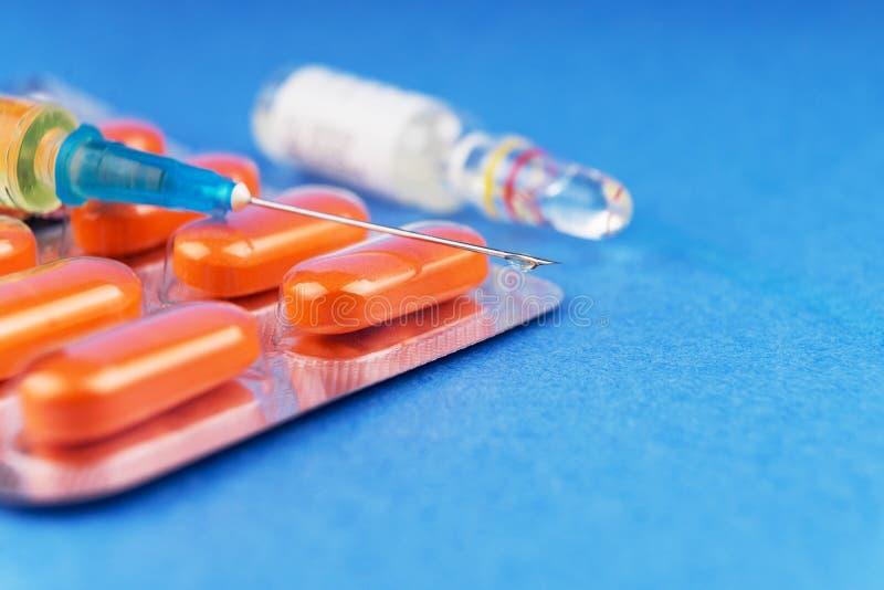 Tabuletas em uma bolha, em uma seringa com a preparação médica datilografada e em uma ampola com uma preparação farmacêutica dope fotografia de stock royalty free