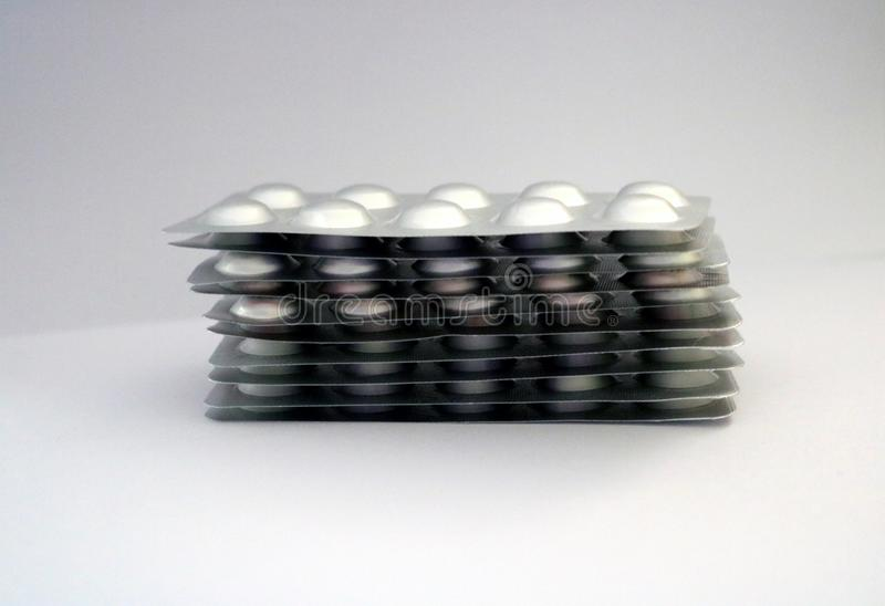 Tabuletas embaladas nas tiras de alumínio de alumínio do bloco de bolha com fundo branco foto de stock royalty free