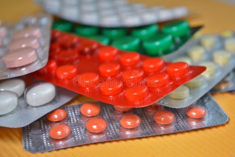 Tabuletas médicas amarelas, brancas, vermelhas, verdes no bloco, tabuletas embaladas nas bolhas no fundo amarelo imagem de stock