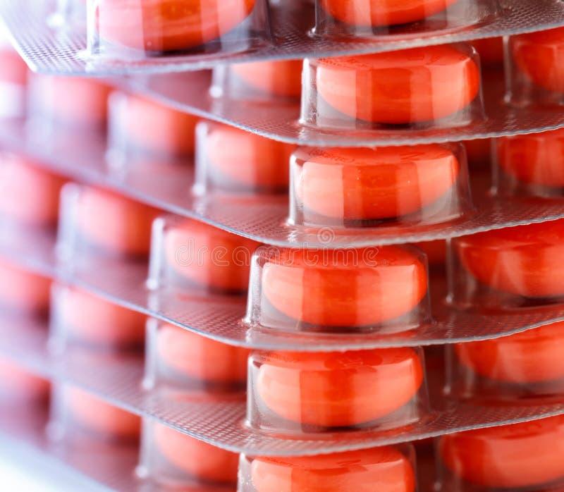 Tabuletas vermelhas na embalagem plástica imagem de stock royalty free