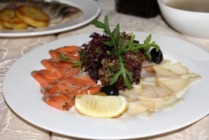 Taca z uwędzoną pokrojoną rybą, garnirującą z cytryną, oliwkami i sałatką, Kawałki łosoś i dymiąca biała maślana ryba - ryba obrazy royalty free