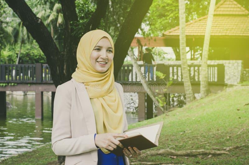Taccuini di condizione e della tenuta della donna del muslimah del fronte di sorriso giovani in parco Spazio negativo per testo fotografie stock libere da diritti