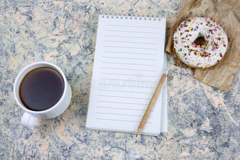 taccuino alto falso con lo strato di Libro Bianco dello spazio in bianco, la tazza di caffè e la ciambella immagini stock
