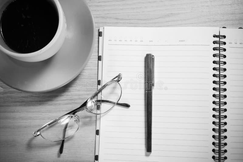 Taccuino aperto con la penna, i vetri ed il caffè su fondo di legno fotografia stock libera da diritti