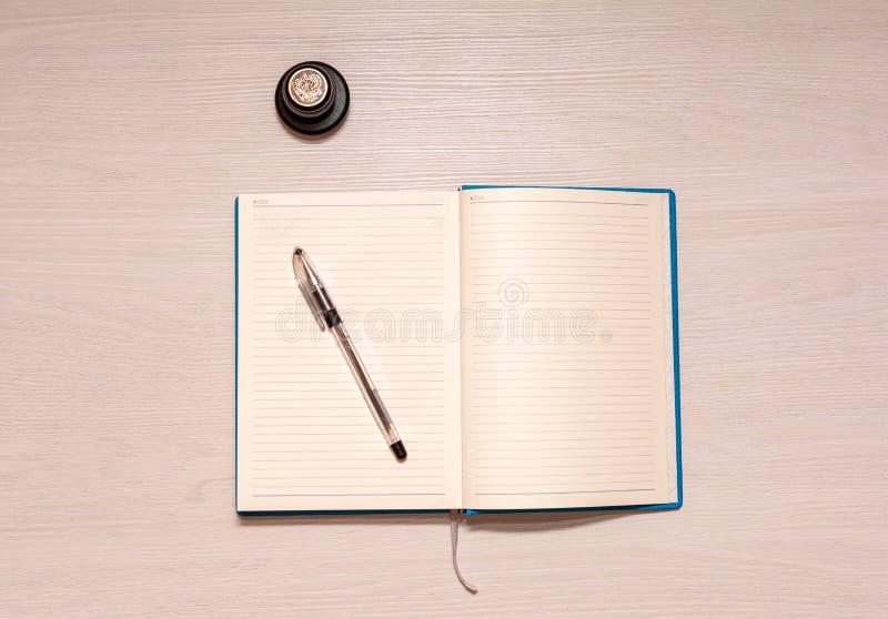 Taccuino aperto con la penna nera ed il bollo ufficiale su una tavola di legno bianca, vista superiore fotografia stock