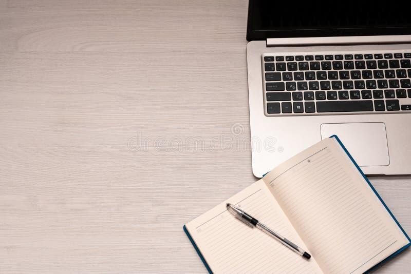 Taccuino aperto con la penna nera ed il computer portatile d'argento su una tavola di legno bianca, vista superiore, spase della  immagine stock