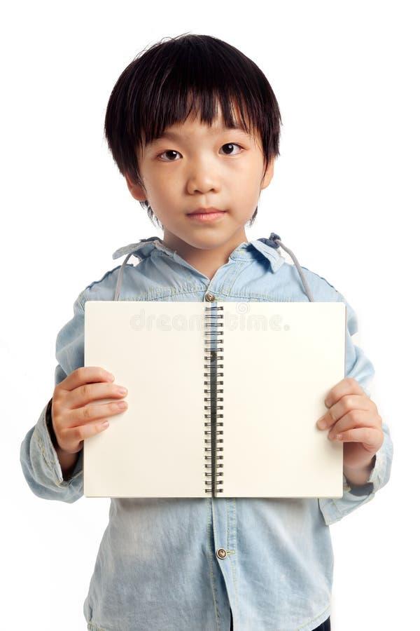 Taccuino aperto della tenuta asiatica del ragazzo fotografia stock libera da diritti