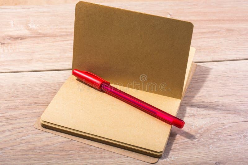Taccuino aperto di colore di Brown e una penna fotografie stock libere da diritti
