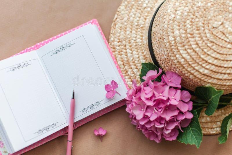 Taccuino aperto femminile con la penna, i fiori dell'ortensia ed il cappello di paglia rosa Posto di lavoro romantico per sognare immagine stock libera da diritti