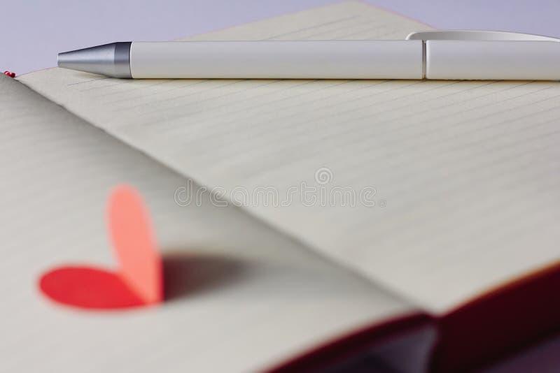 Taccuino in bianco aperto, penna e cuore di carta rosso fotografia stock libera da diritti