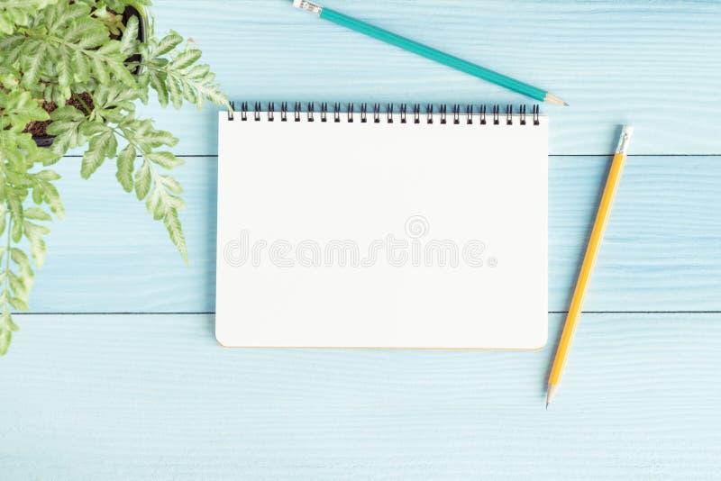 Taccuino in bianco con e matita su fondo blu, foto piana di disposizione del taccuino per il vostro messaggio immagine stock