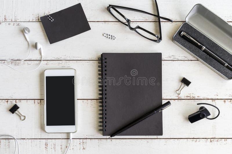 Taccuino in bianco con il cellulare sull'ufficio dello scrittorio immagine stock libera da diritti