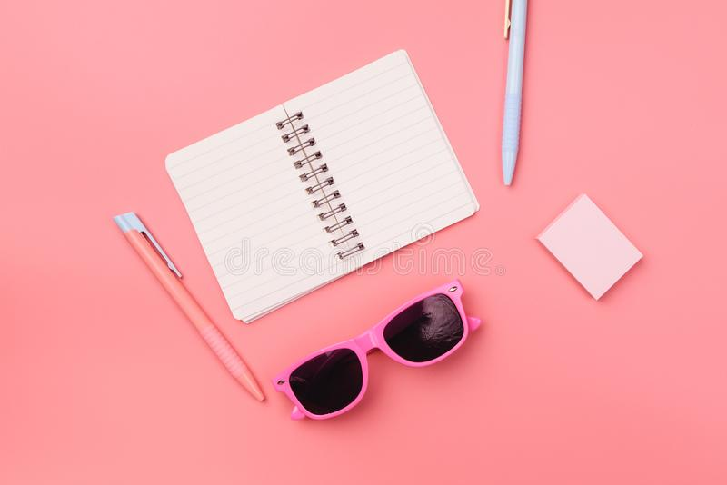 Taccuino in bianco con la penna e nota appiccicosa sopra pastello rosa d fotografia stock libera da diritti