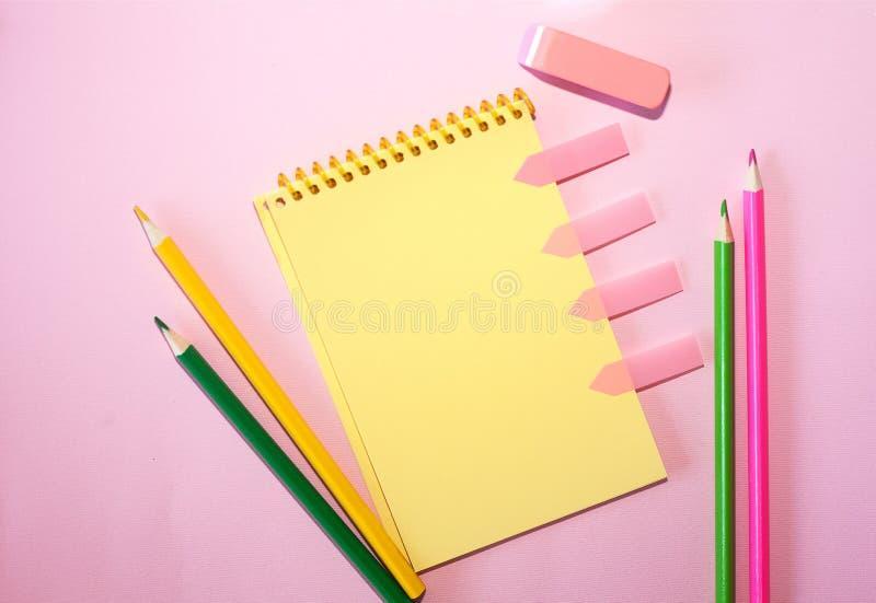 Taccuino in bianco con le matite colorate contro fondo pastello rosa Disposizione piana, vista superiore immagine stock