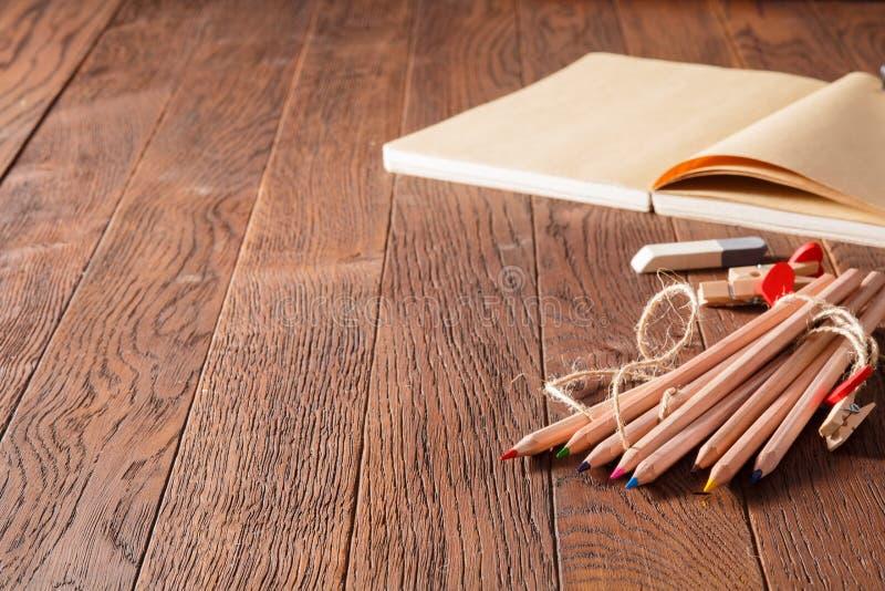 Taccuino in bianco e matite variopinte sulla tavola di legno Gomma e perni di legno fotografia stock libera da diritti