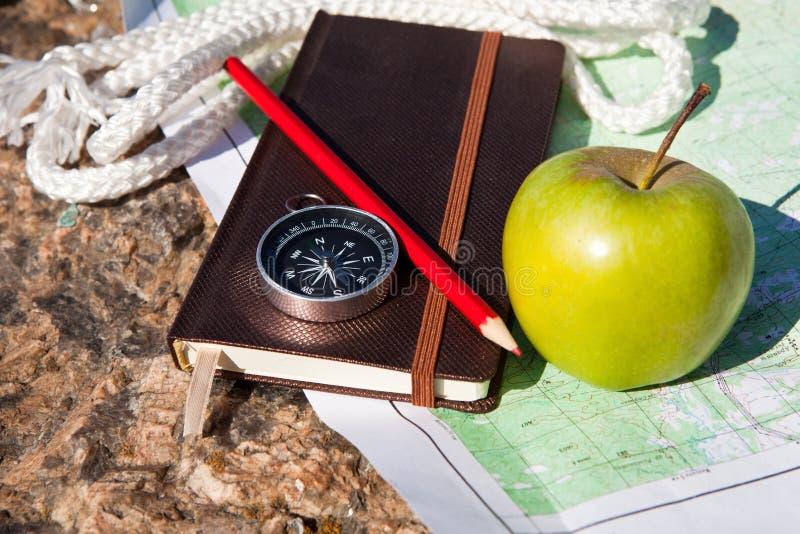 Taccuino, bussola, mela, corda su fondo di pietra immagini stock