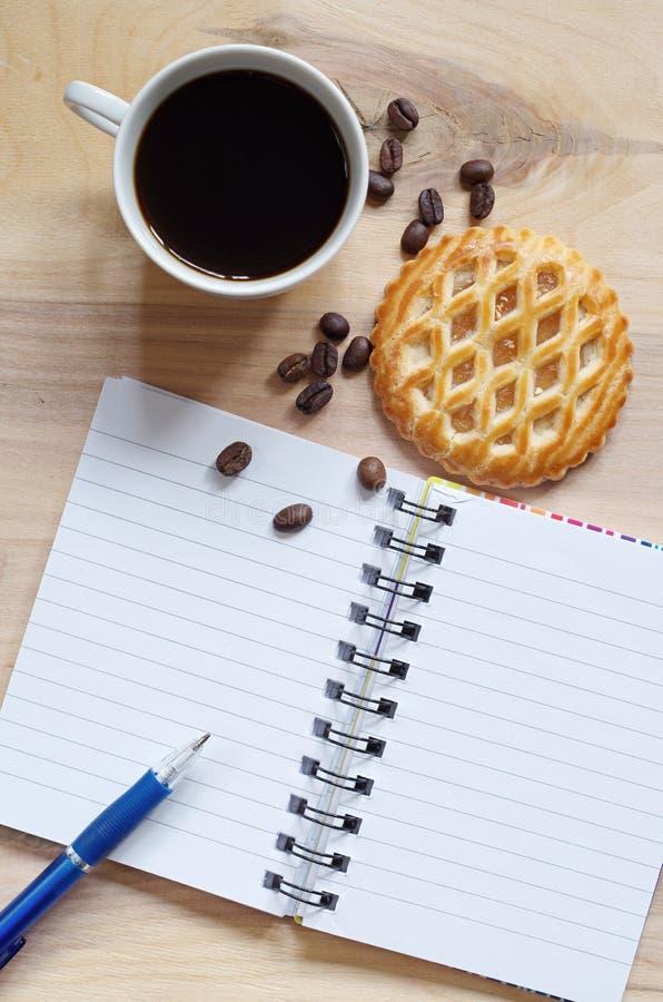 Taccuino, caffè e dolci con il ripieno di mele fotografia stock