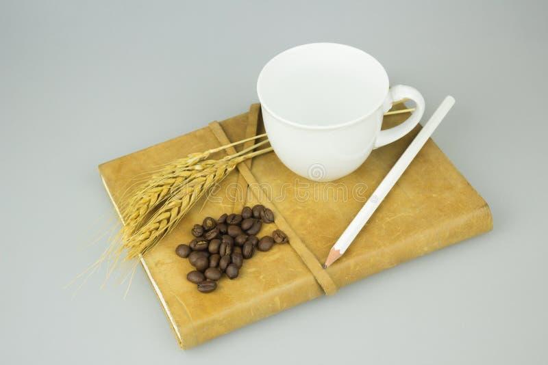 Taccuino con il fondo dell'isolato della tazza di caffè e della matita fotografie stock libere da diritti