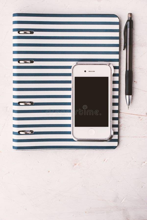 Taccuino con la penna e telefono sul verticale bianco della tavola immagine stock libera da diritti