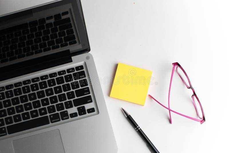 Taccuino con la penna nera, blocchi note variopinti sullo scrittorio, vetri sullo scrittorio con la penna e tazza di caffè, tasti fotografia stock