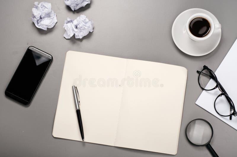Taccuino con la penna, tazza di caffè, vetri, smartphone e sgualcito fotografia stock