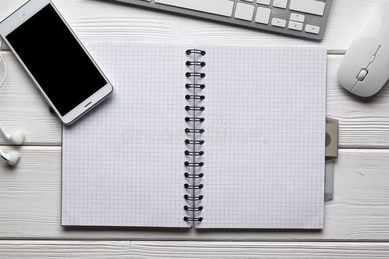Taccuino con lo spazio della copia, lo smartphone moderno, le cuffie, la tastiera di computer ed il topo sulla tavola di legno fotografie stock libere da diritti