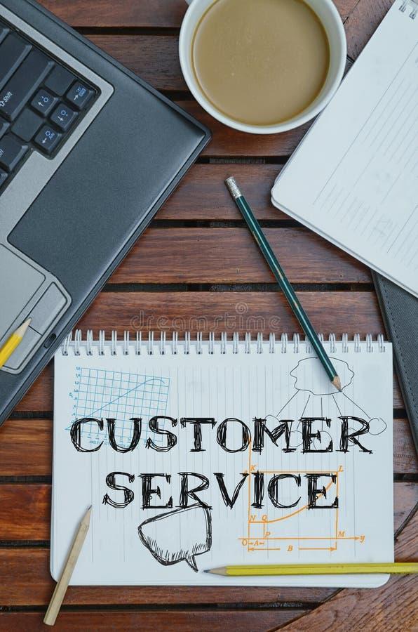 Taccuino con testo dentro servizio di assistenza al cliente sulla tavola con caffè, immagini stock libere da diritti