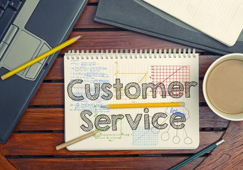 Taccuino con testo dentro servizio di assistenza al cliente sulla tavola con caffè, immagini stock