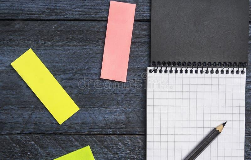 taccuino con uno strato in una gabbia con la matita e note appiccicose colorate su un fondo rustico di legno, fine su, vista supe immagine stock libera da diritti