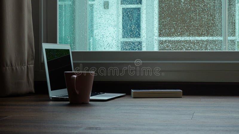 Taccuino del computer accanto ad un caffè della tazza sul fondo della finestra di giorno piovoso fotografie stock