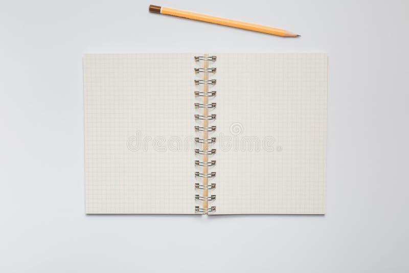 Taccuino della scuola con la matita gialla immagine stock