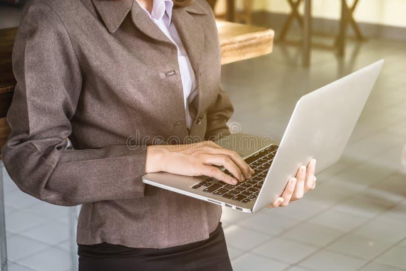 Taccuino della tenuta di condizione e della mano della donna di affari per usando lapt immagine stock