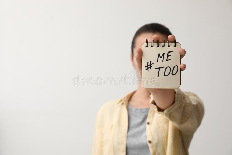 Taccuino della tenuta della donna con hashtag MeToo contro fondo leggero, primo piano Fermi sessuale fotografie stock