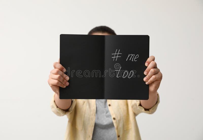 Taccuino della tenuta della donna con il fondo leggero MeToo del hashtag, primo piano Aggressione sessuale di arresto fotografia stock