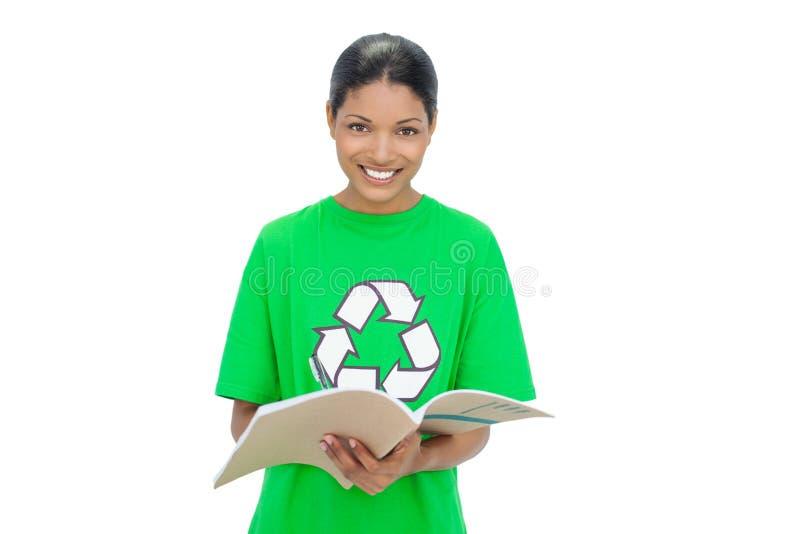 Taccuino di riciclaggio d'uso di modello sorridente della tenuta della maglietta fotografie stock libere da diritti