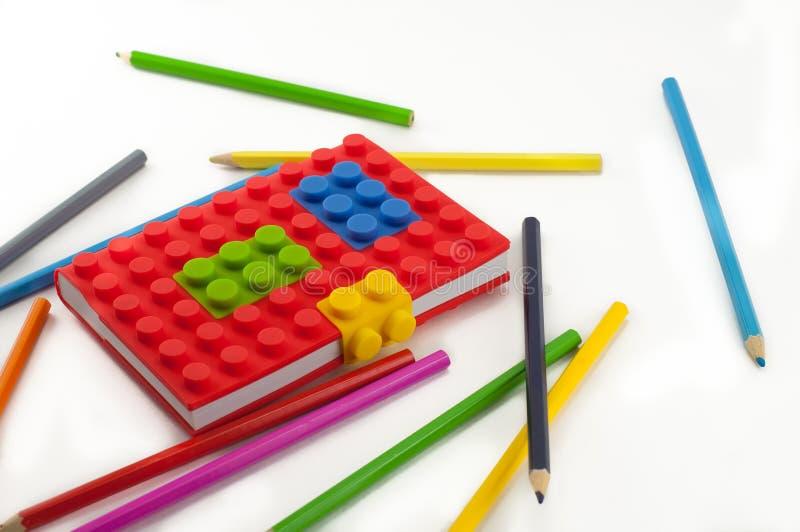 Taccuino e matite colorati su fondo bianco fotografia stock
