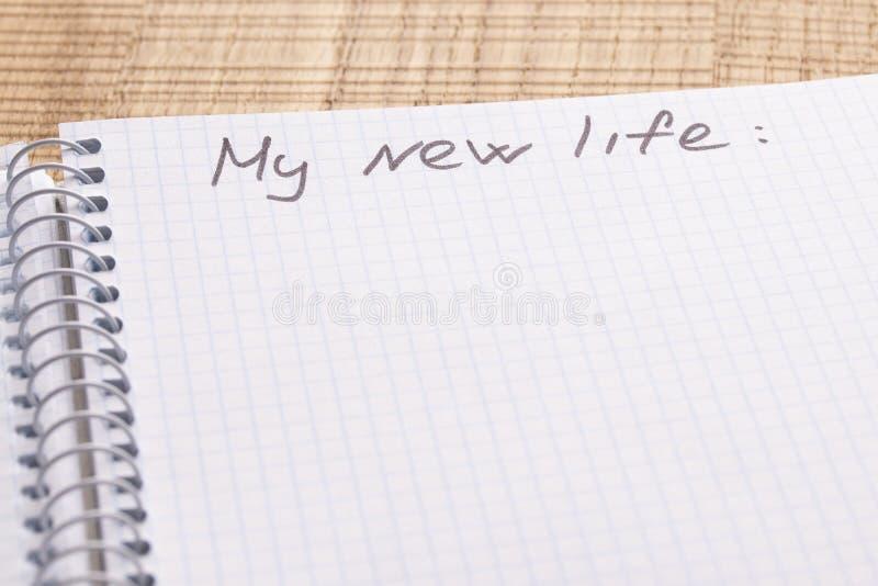 Taccuino e penna del posto di lavoro di vista superiore sul fondo di legno della tavola Iscrizione - la mia nuova vita fotografia stock libera da diritti