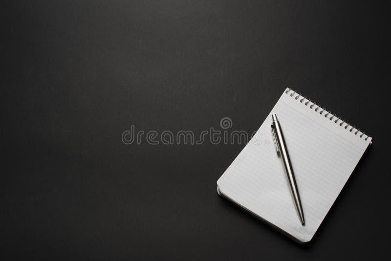 taccuino e penna su una tavola nera fotografie stock libere da diritti