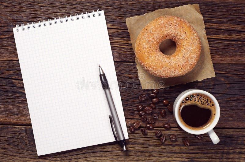 Taccuino e tazza di caffè con la ciambella fotografia stock libera da diritti