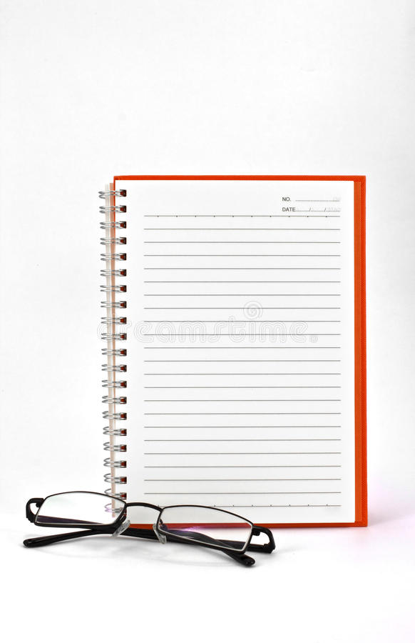 Taccuino ed occhiali arancioni immagine stock