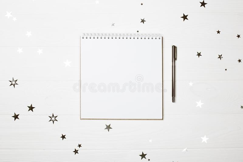 Taccuino a forma di quadrato bianco con la penna su fondo di legno pastello immagine stock libera da diritti