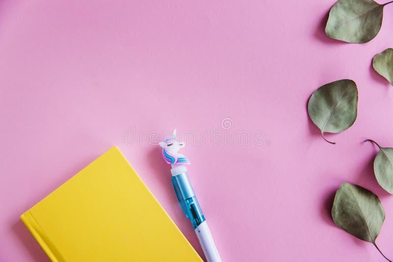 Taccuino giallo per le note, la penna divertente dell'unicorno e le foglie verdi dell'eucalyptus su fondo pastello rosa Disposizi fotografie stock