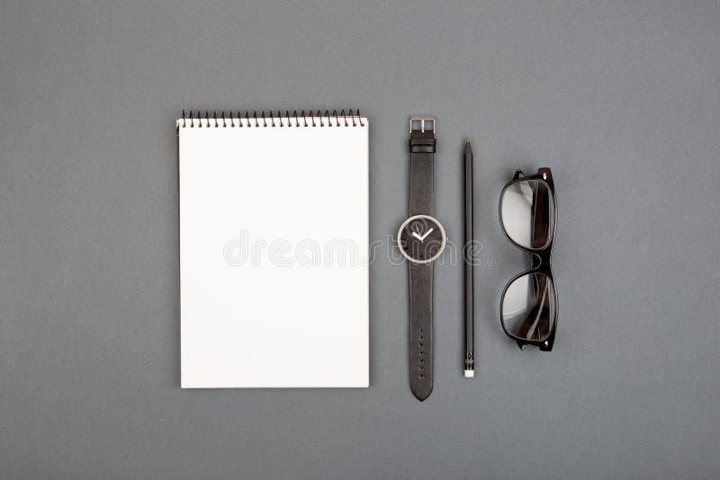 taccuino, matita, orologio e vetri in bianco a spirale sul backgro grigio fotografia stock