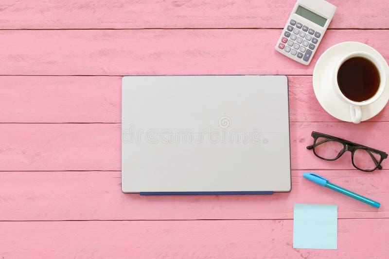Taccuino o computer portatile del computer disposto sulla tavola di legno rosa vicino al fotografia stock libera da diritti