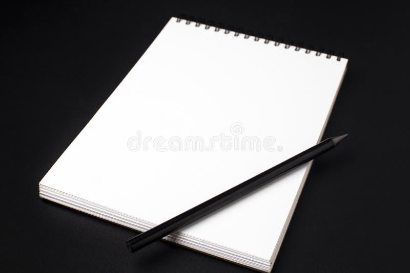 Taccuino o sketchbook pulito aperto con la matita sul backgro nero fotografia stock libera da diritti
