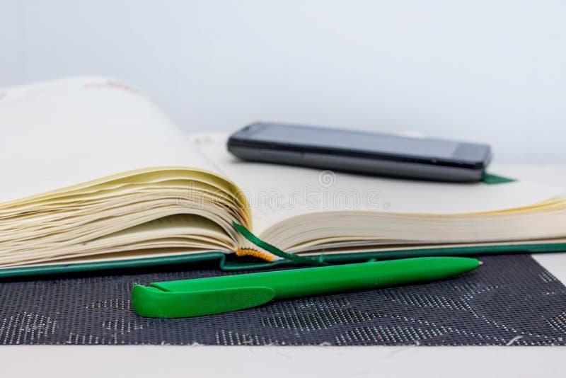 Taccuino, penna e telefono - mezzi di informazioni di registrazione durante fotografia stock