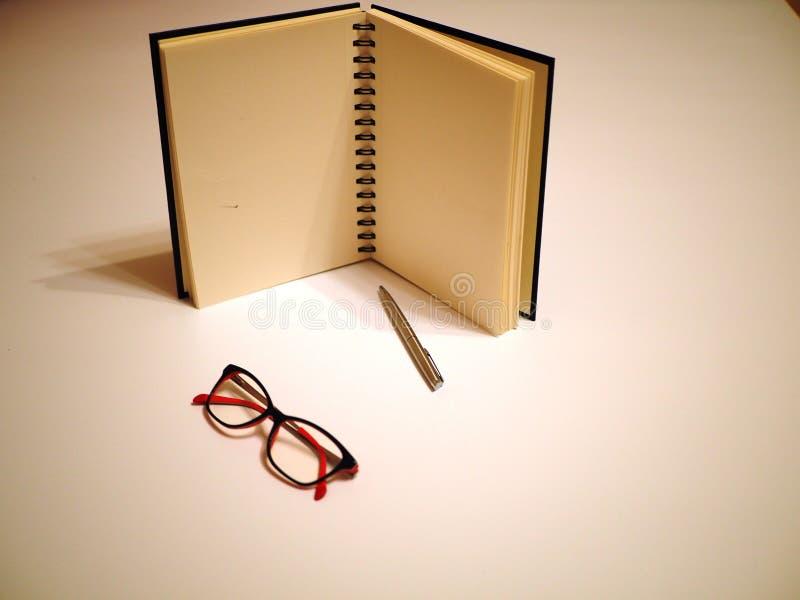 Taccuino, penna e vetri su una tavola bianca immagine stock