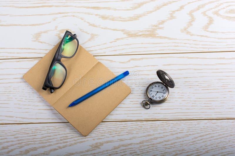 Taccuino, penna, orologio da tasca ed occhiali da sole in bianco di colore di Brown immagini stock libere da diritti