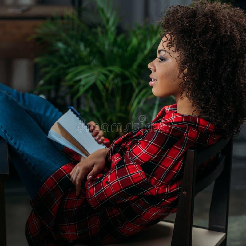 Taccuino pensieroso della tenuta della giovane donna con la penna e distogliere lo sguardo fotografia stock libera da diritti